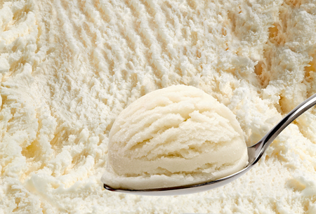 Spoon of vanilla ice cream on ice cream background