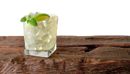 Caipirinha cocktail with lime wedge on the log in rocks glass with white background Stock Photo