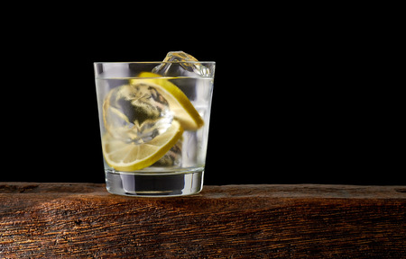 Gin tonic with lemon on wooden table with black background