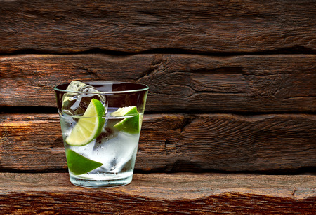 Gin and tonic with lime wedges on wooden table background