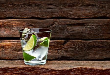 Gin tonic con rodajas de limón en el fondo de la mesa de madera