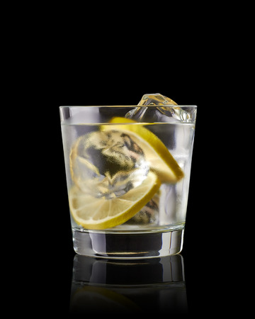 Vodka Lime, gimlet or gun tonic with ice in glass on black background