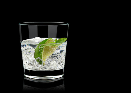 Vodka tonic with lime wedge or gun ice in rocks glass on black background