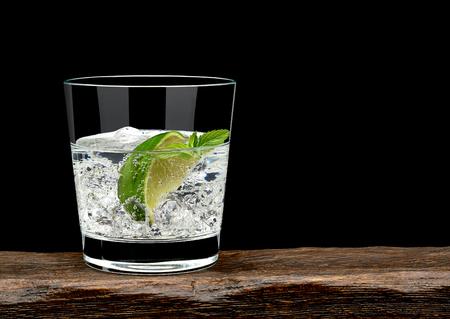 gin tonic con rodaja de limón y hielo en vaso bajo de mesa de madera y fondo negro con el espacio de la copia