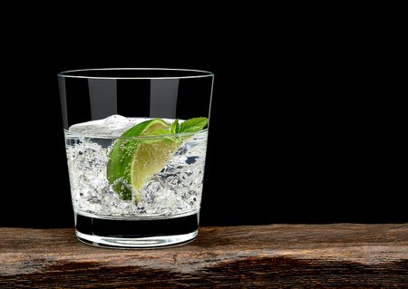 lime: Gin tonic with lime wedge and ice in rocks glass on wooden table and black background with copy space