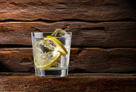 gimlet: Gin and tonic with lemon on wooden table background
