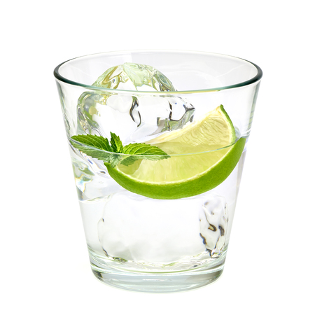 Gin tonic cocktail and lime wedge on white background