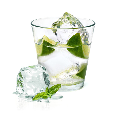Vodka with ice and lime wedge isolated on white background Imagens