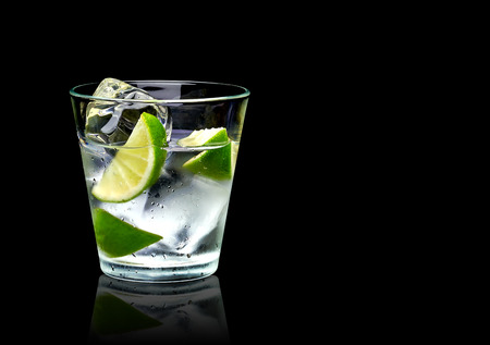 Vodka lime or gin tonic with ice in rocks glass on black background