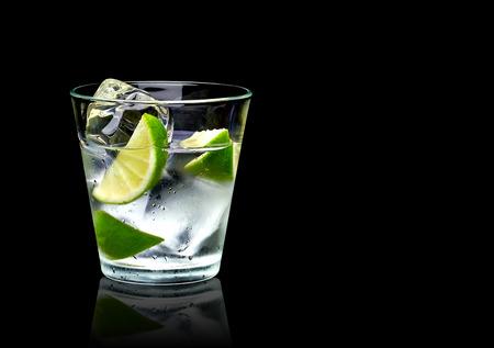 Vodka calce o gin tonic con ghiaccio in rocce di vetro su sfondo nero