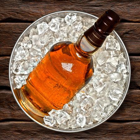 botella de whisky: Botella de whisky en el cubo de hielo vista superior sobre fondo de madera