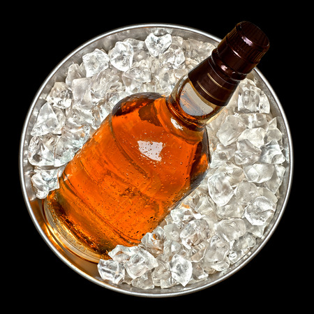 soda water: Whiskey bottle in ice bucket top view on black background