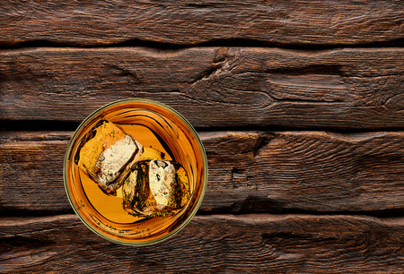 shooter drink: Whiskey with ice cubes in rocks glass on log table