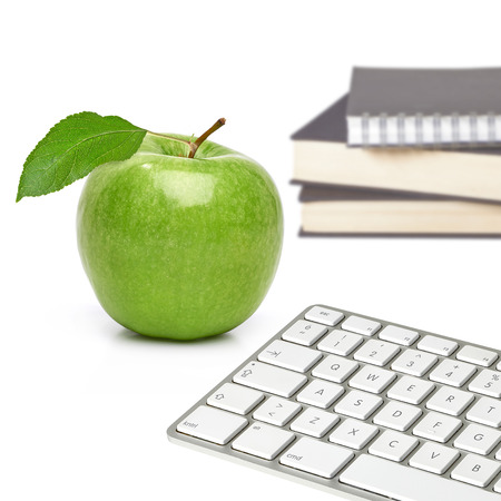 Green apple, books and computer keyboard on white backgr?und Stock Photo