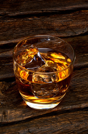 Glass of whiskey on wooden table.