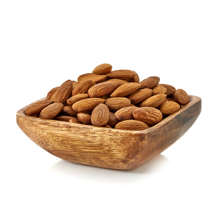 Almonds in wooden bowl on white background. Stock Photo