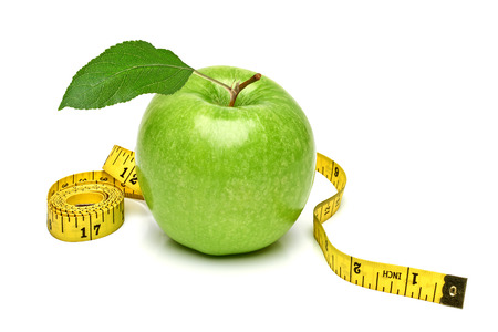 Green apple with measuring tape on white background.