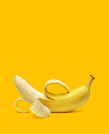 Peeled banana on yellow background with copy space. Stock Photo