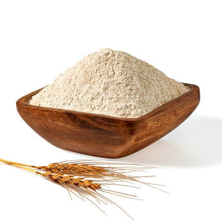 Whole flour in wooden bowl with wheat ears on white background.