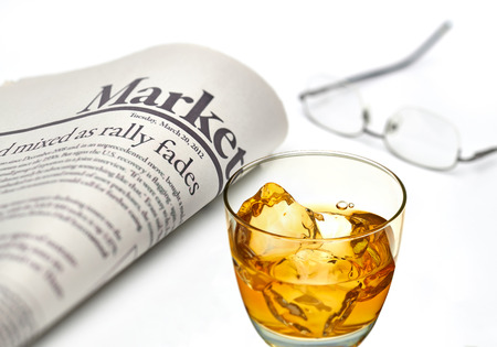 gazette: Economy newspaper with whiskey glass on white background in shallow depth of field Stock Photo