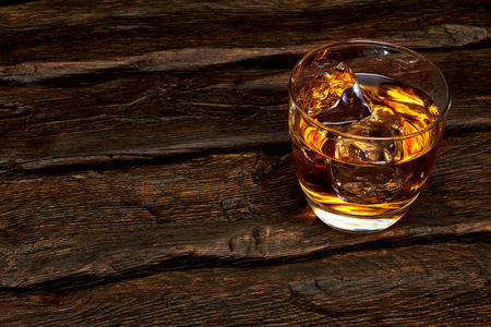 whiskey on the rocks: Whiskey in rocks glass with ice cubes on the log table