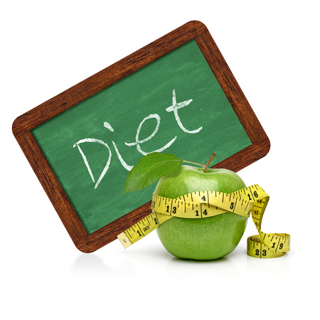 regimen: Green apple and measuring tape with diet chalkboard sign on a white background