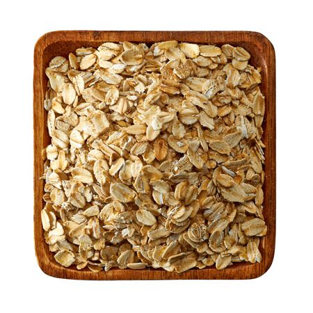 wild oats: Oat flakes in wooden bowl from top Stock Photo