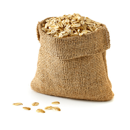 processed grains: Oat flakes in sack on white background