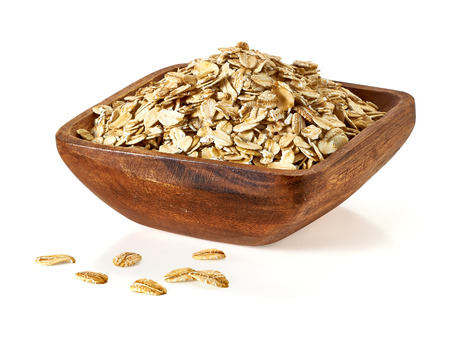 wild oats: Oat flakes in wooden bowl on a white background