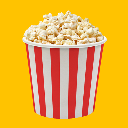 Popcorn in red striped bucket on yellow background