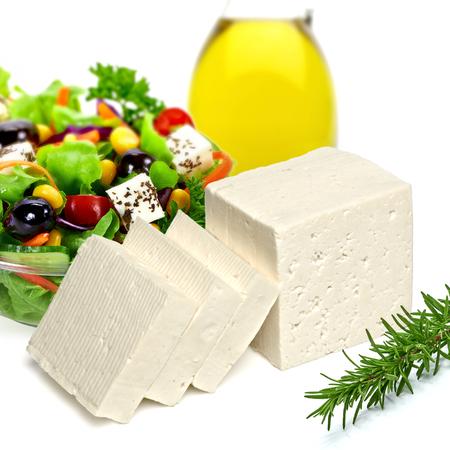 queso fresco blanco: Aceite de oliva con ensalada y queso feta sobre fondo blanco