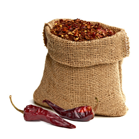 crushed red peppers: Crushed red pepper pimienta roja in the sack with dried chili peppers on white background Stock Photo