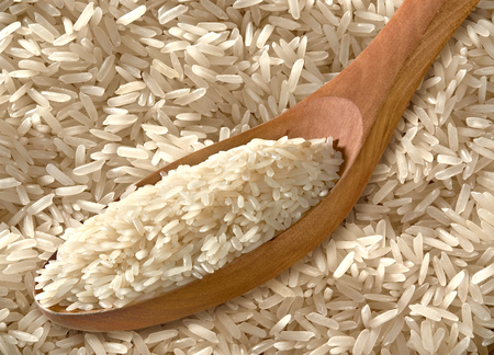 bleed: Rice in Wooden Spoon on Full Bleed Rice Background