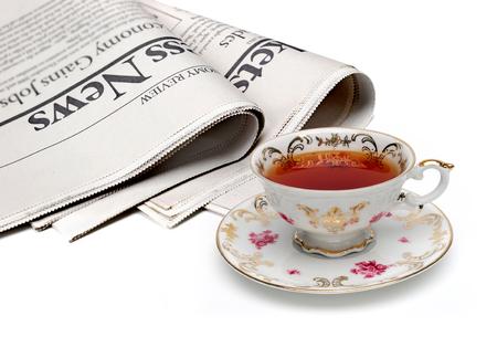 tasse de thé antique et le journal sur fond blanc