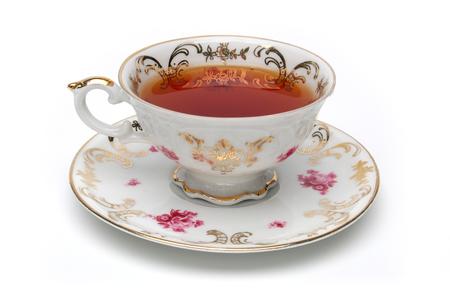 Tasse à thé antique pleine de thé sur fond blanc
