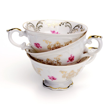 antique background: Antique tea cups on a white background. Stock Photo