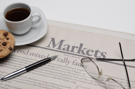 gazette: Economy newspaper with cup of coffee on a white background in shallow depth of field