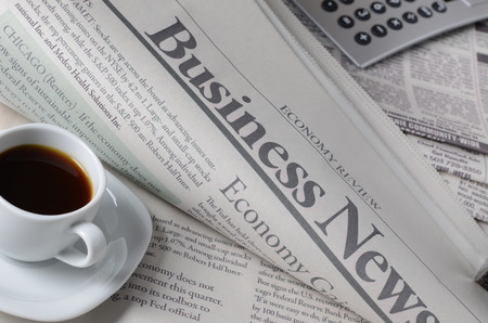 Economy newspaper with cup of coffee on a white background in shallow depth of field