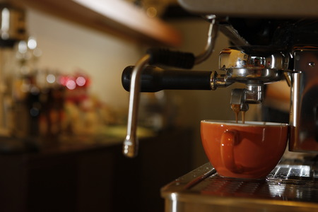 midsection: Midsection of barista making cappuccino at counter in coffeeshop