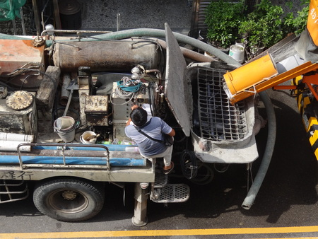 Cement truck operator supervise pouring cement into the cement pump Stock Photo