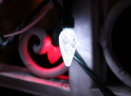 A single Christmas lights lightbulb with ornate fence in the back Stock Photo