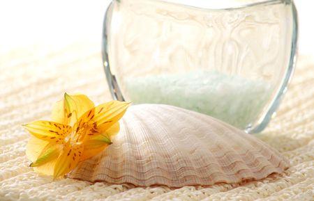 Bath salt, seashell and flowers on towel