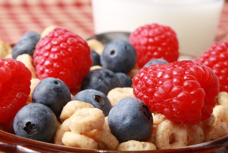 Blueberries and raspberries with cereal and milk