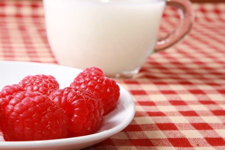 Milk and berries on checkered tablecloth Stock Photo