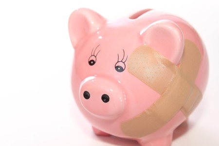 Pink piggy bank with bandage