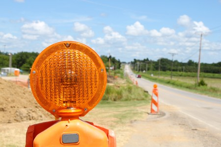Orange road construction flashers on a long country road Imagens