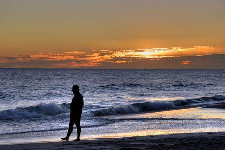 hombre solo: Hombre caminando sobre una puesta de sol de playa Foto de archivo