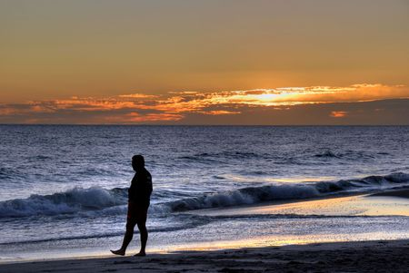 blue sky thinking: Man walking on a sunset beach Stock Photo
