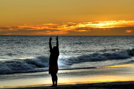 reverence: Man on the beach at sunset Stock Photo