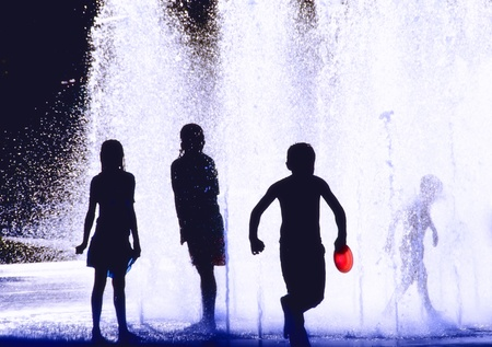 Silhouettes of Children Playing in a fountain photo